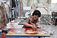 A woman works on a lacquer painting in a studio, Ho Chi Minh City, Southeast Asia. Lacquer painting, son mai in Vietnamese, was developed as its own art form separate from wood finishing and is an important traditional technique taught in the Fine Arts University of Ho Chi Minh City.