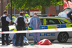 ©Licensed to London News Pictures 21/08/2020             Plumstead, UK. A forensic officer and police with the body. Parts of Plumstead high street in South East London are closed this morning after a man was fatally stabbed to death. It is believed the man was stabbed on Heron Hill a short distance away then transferred to Plumstead for the air ambulance. Photo credit: Grant Falvey/LNP