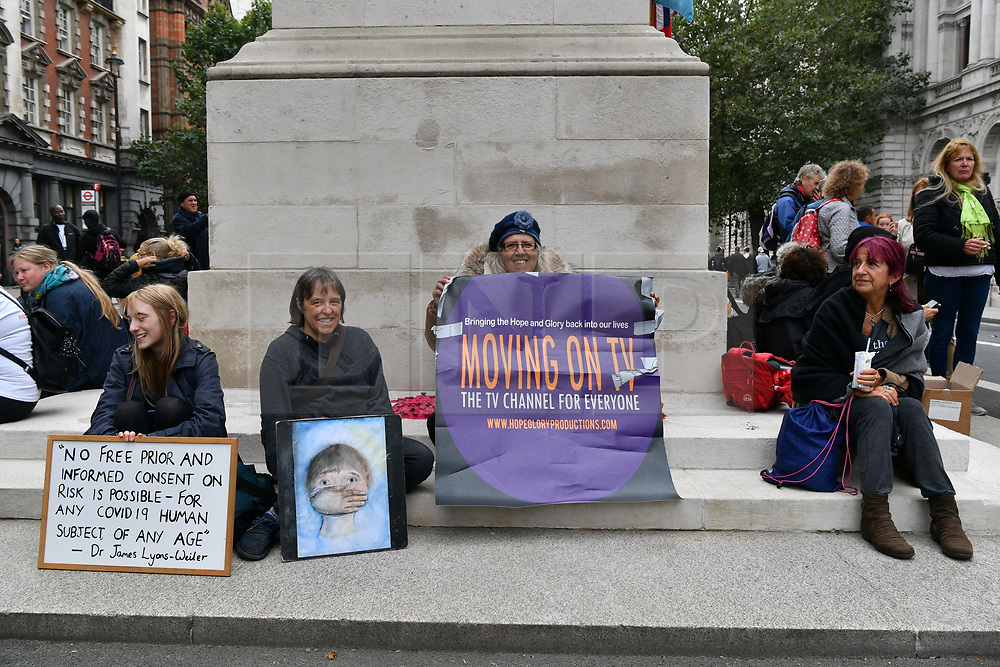 © Licensed to London News Pictures. 29/08/2020. London, UK. Protesters sit on the Cenotaph war monument outside Downing St taking part in a demonstration organised by Stand Up X organisation in London, United Kingdom on August 29, 2020.  The group is against the British government policy of Covid-19 measures including mask wearing, vaccinations and lockdown. Photo credit: London News Pictures
