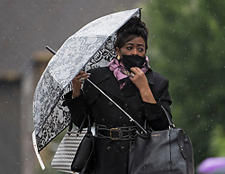 © Licensed to London News Pictures. 13/06/2021. London, UK. A woman shelters underneath an umbrella in wet conditions at Queens Park in north west London at rush hour, on another grey and damp summer's day. Photo credit: Ben Cawthra/LNP