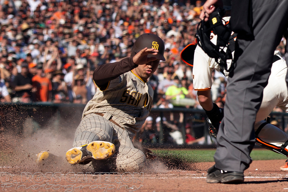 San Diego Padres pinch runner Javy Guerra, left, slides safely home past San Francisco Giants catcher Curt Casali (2) on a sacrifice fly by Manny Machado during the eighth inning of a baseball game, Saturday, Oct. 2, 2021, in San Francisco. (AP Photo/D. Ross Cameron)