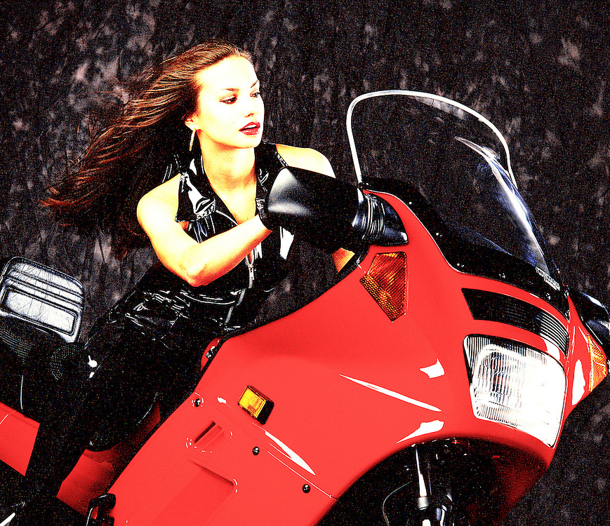 """A beautiful young woman in a black catsuit astride a red sport motorcycle. -- To determine pricing and license this image simply click """"Add To Cart"""" below --"""