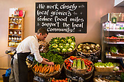 A male shop keeper arranges the carrots in a fruit and vegetable display within a connivence shop in Wadebridge, North Cornwall, United Kingdom.  The shop works closely with local growers and suppliers to reduce food miles and support the local community.  Wadebridge has a grass roots social enterprise called Wadebridge Renewable Energy Network (WREN) which supports local businesses and aims to become the first renewable energy powered town in the UK.