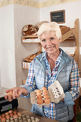 Portrait of a vendor arranging eggs in egg carton in the shop and smiling, Bavaria, Germany,