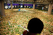 Visitors look at a scaled model of the Shanghai city center at the Urban Planning Museum in Shanghai, China on 25 October 2010.  The Jinmao tower is in the foreground.  Shanghai, China's largest city, is quickly becoming one of the major financial centers of the world.
