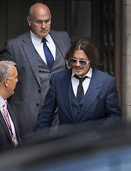 © Licensed to London News Pictures. 07/07/2020. London, UK. US actor Johnny Depp smiles as he leaves The High Court in Central London surrounded by his security team. Johnny Depp's libel trial against The Sun newspaper is due to take place over the next three weeks over allegations he was violent and abusive towards his ex-wife Amber Heard. Photo credit: Peter Macdiarmid/LNP