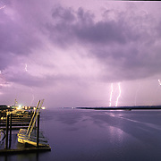 Lightning flashes over docks and sailboats on Banks Channel in Wrightsville Beach, NC.