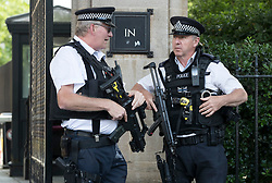 © Licensed to London News Pictures. 22/06/2017. London, UK. Armed police stand guard as colleagues hold a man who earlier was tasered near an entrance to Parliament. Photo credit: Peter Macdiarmid/LNP