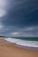 Dark and stormy skies loom over a pristine beach along the Great Ocean Road in Australia.
