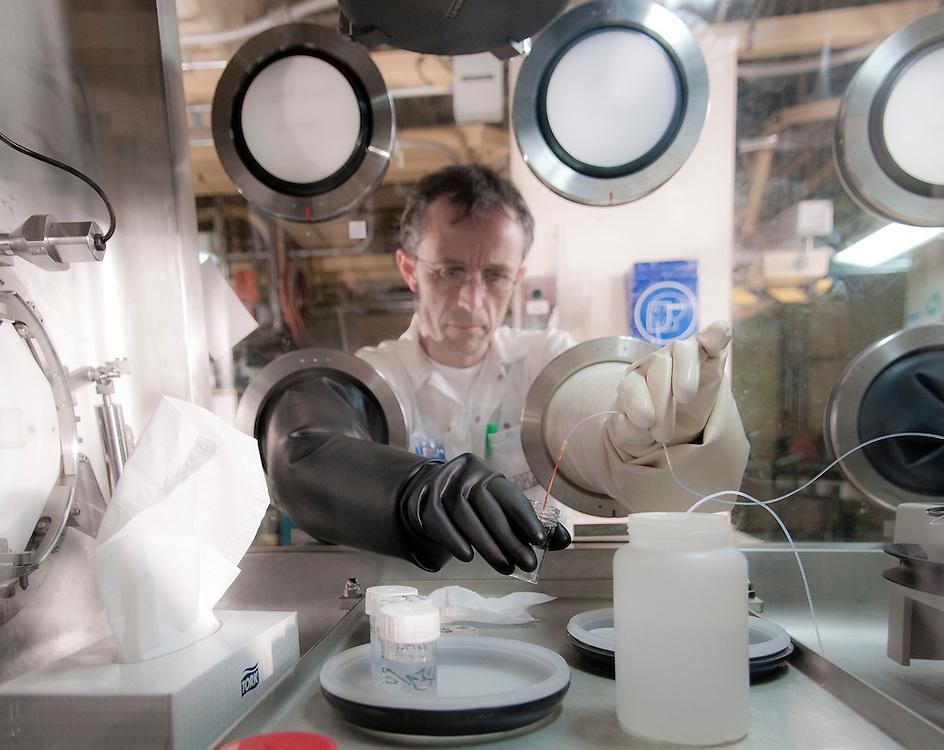 "Laboratory Analyst, Valery Le Magnent, working on a glovebox radiometric analysis station in the laboratories of the UP3 facility of the AREVA La Hague site in Normandy, France.<br /> Valery Le Magnent, analyste de laboratoire, travaillant sur un des postes d'analyses radiometrie ""Boites a gants"" dans les laboratoires de Controle de Marche du site UP3 du site AREVA La Hague en Normandie, France."