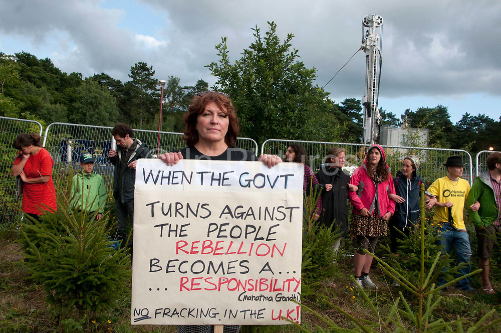 Balcombe, West Sussex. Site of Cuadrilla drilling. Demonstration against fracking 18.08.2013. Protesters surround the site and link arms and a woman demonstrator holds a poster quoting Gandhi (When the government turns against the people, rebellion becomes a responsibility ) and saying No Fracking in the UK'.