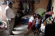 """""""Manteca"""", _lard in English_  watches the reaction of three women after he notified them of the murder of a relative, Guatemala City,  Monday, June 23, 2009. Manteca, a funeral service salesman, went to the slum where the man was murdered to collect address and other information on the relatives in hopes of selling them a wake-coffin-burial package."""