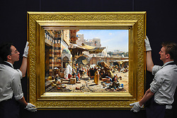 "© Licensed to London News Pictures. 11/10/2019. LONDON, UK. Technicians present ""Market in Jaffa"", 1887, by Gustav Bauernfeind, (Est GBP2.5-3.5m).  Preview of works from the Najd Collection of orientalist paintings at Sotheby's in New Bond Street, which record daily life in the historic Arab, Ottoman and Islamic worlds  All 155 paintings are on public view 11- 15 October, with 40 works to be auctioned on 22 October.  Photo credit: Stephen Chung/LNP"