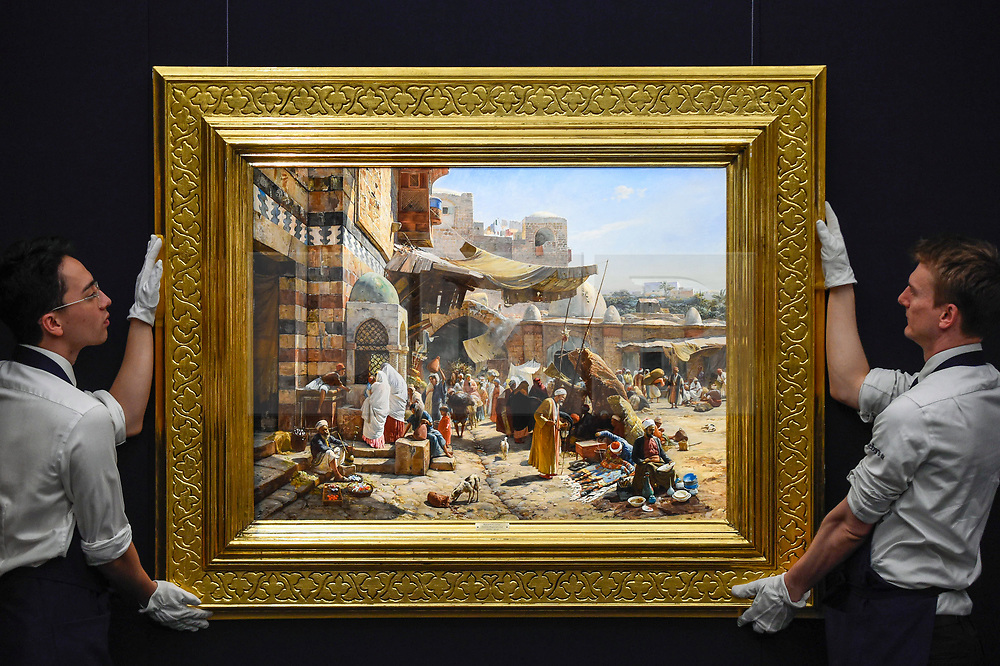 """© Licensed to London News Pictures. 11/10/2019. LONDON, UK. Technicians present """"Market in Jaffa"""", 1887, by Gustav Bauernfeind, (Est GBP2.5-3.5m).  Preview of works from the Najd Collection of orientalist paintings at Sotheby's in New Bond Street, which record daily life in the historic Arab, Ottoman and Islamic worlds  All 155 paintings are on public view 11- 15 October, with 40 works to be auctioned on 22 October.  Photo credit: Stephen Chung/LNP"""