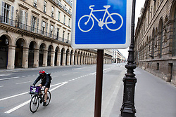 Cyclist wearing face mask on Rivoli Street next to circulation sign for cycle track in Paris on May 4, 2020, on the forty-ninth day of a strict lockdown in France, in place to attempt to stop the spread of the new coronavirus (COVID-19). Photo by Raphael Lafargue/ABACAPRESS.COM