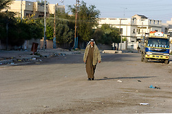 Iraqi Civilian man walks through the Basra City as the early Iraqi commuter morning rush hour begins passing British Troops who are carrying out an IED sweep in the area. March 2005