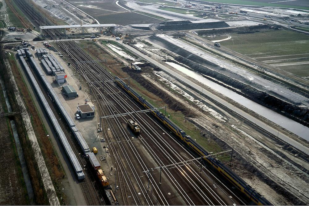 Nederland, Oude Moerdijkpolder, 08-03-2002;  spoor emplacement rond Station Lage Zwaluwe, direct rechts vh bestaande spoor komt de HSL te lopen, aan de horizon Bredase Dijk: aanleg van viaduct (met landhoofden) waarmee de (nieuwe) sporen overgestoken zullen worden, bestaande overweg komt te vervallen; rechtsboven: de A16 / A59, deze wordt ih kader van de HSL aanleg ook gereconstrueerd en krijgt 2 x 3 rijstroken; infrastructuur verkeer en vervoer spoor intercity trein mobiliteit transport rangeerterrein wegenbouw landschap (zie ook Bredase dijk);<br /> luchtfoto (toeslag), aerial photo (additional fee)<br /> foto /photo Siebe Swart