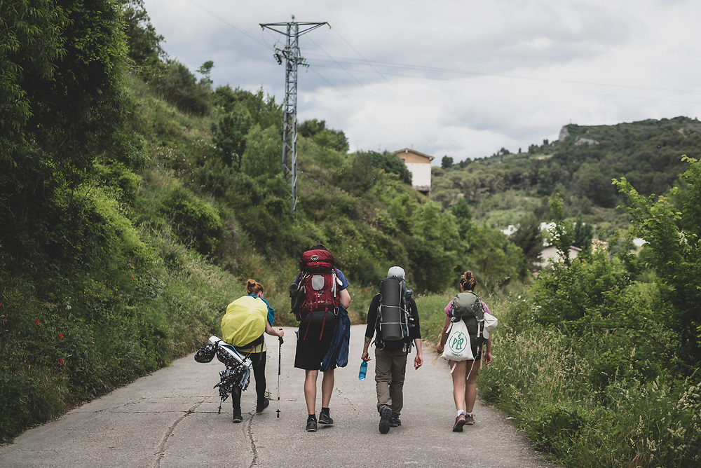 Iveta from Germany, Alex from the USA, Falk from Germany, and Marie from Germany approach the town of Estella as they complete the day's walk on the Camino de Santiago in the Navarre region of Spain.<br /> <br /> (June 4, 2018)
