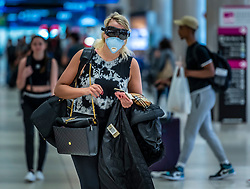 A masked and goggled traveler moves through Miami International Airport at the start of the pandemic.