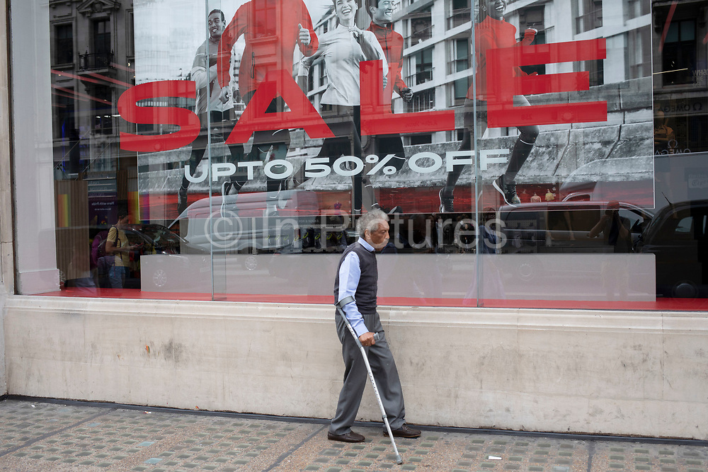 Man struggling with crutches walks gingerly past a shop selling fitness clothing as pictures of models exercise on the shop window in London, United Kingdom.
