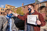 "16 OCTOBER 2020 - PERRY, IOWA: A Biden / Harris campaign volunteer takes the temperature of an attendee and conducts a COVID questionnaire as people walk into a ""Get Out the Vote"" event with Doug Emhoff, the husband of Vice Presidential Candidate Kamala Harris. Emhoff spoke to a group of about 30 people. The crowd was socially distanced and masks were required in  keeping with CDC and state of Iowa health guidelines to deal with the COVID-19 pandemic. Emhoff is traveling throughout Nebraska and Iowa today, campaigning on behalf of the Biden/Harris ticket.        PHOTO BY JACK KURTZ"