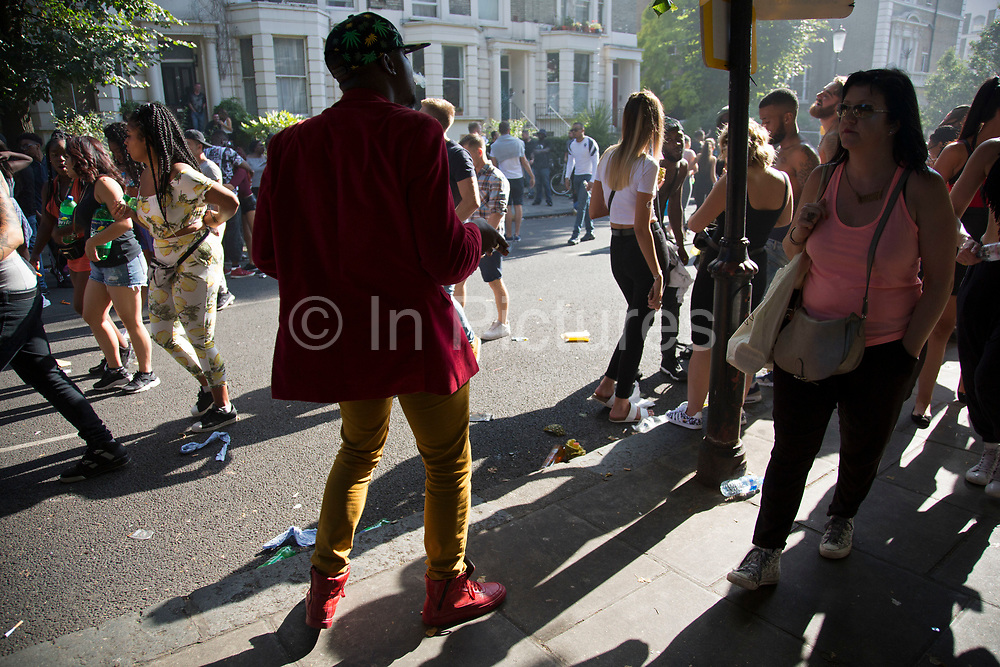 Crowds gather in the evening light on Monday 28th August 2016 at the 50th Notting Hill Carnival in West London. A celebration of West Indian / Caribbean culture and Europes largest street party, festival and parade. Revellers come in their hundreds of thousands to have fun, dance, drink and let go in the brilliant atmosphere. It is led by members of the West Indian / Caribbean community, particularly the Trinidadian and Tobagonian British population, many of whom have lived in the area since the 1950s. The carnival has attracted up to 2 million people in the past and centres around a parade of floats, dancers and sound systems.