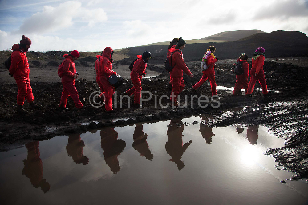 Hundreds of environmental activists stopping the open cast coal mine Ffos-y-Fran near Merthyr Tydfil, Wales from operating May 3rd 2016. Unchallenged by security the activists enter the mine which is not in operation and empty for any other activity.The activists from Reclaim the Power wants the mine shut down and a moratorium on all future open coal mining in Wales. The group Reclaim the Power had set up camp near by and had over three days prepared the action and up to 300 activists all dressed in red went into the mine in the early morning. The activist were plit in three groups and carried various props signifying the red line in the sand, initially drawn in Paris at the COP21. The mine is one of the largest open cast coal mines in the UK and is run by Miller Argent who have to date extracted 5million tons of coal. The activists entered the mine unchallenged by any security or police and the protest went on peacefully till mid afternoon with no arrests made.  Open coal mining is hugely damaging to the local environment and  contributing to global climate change.