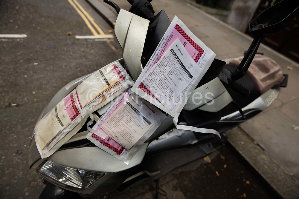 Scooter festooned with traffic tickets in Finsbury Circus, City of London.
