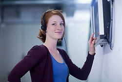 Young female engineer wearing headset and working on touchscreen computer monitor in an industrial plant, Freiburg im Breisgau, Baden-Wuerttemberg, Germany