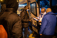 An african migrants shows his ticket to  night bus driver to get on the bus that would him to France. Irun (Basque Country). March 11, 2021. As the number of migrants arriving on the coasts of southern Spain incresead, more and more migrants are heading north to the border city of Irun on their way to reach France, Belgium or other European countries, but the controls of the French police make it difficult for them to pass. (Gari Garaialde / Bostok Photo)