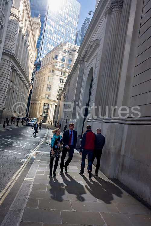 Lunchtime City workers on Lothbury Street in the City of London, the capital's financial district and oldest quarter. The scene is at a slight angle to emphasize the narrow lane that runs alongside the rear walls of the Bank of England, right. Reflected light from plate glass windows, seen at the top, lunchtime passers-by walk under the architecture and powerful influence of financial and banking institutions. Lothbury runs from Gresham Street to Bartholomew Lane and Throgmorton Street. The area was populated with coppersmiths in the Middle Ages before later becoming home to a number of merchants and bankers.