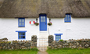 Traditional thatched whitewashed cottage in Porthallow village, Cornwall, England