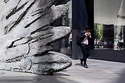 A businessman walks past the sculpture entitled 'City Wing' on Threadneedle Street in the City of London, the capital's financial district, on 17th June 2019, in London, England. This ten-metre-tall bronze sculpture is by President of the Royal Academy of Arts, Christopher Le Brun, commissioned by Hammerson in 2009. 'The City Wing' and has been cast by Morris Singer Art Founders, reputedly the oldest fine art foundry in the world.
