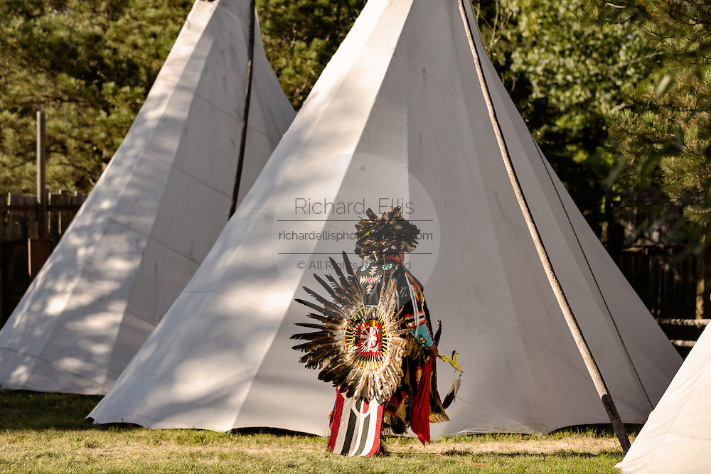 A Native Americans dancer from the Arapahoe people dressed in traditional costume returns to a teepee camp at the Indian Village during Cheyenne Frontier Days July 25, 2015 in Cheyenne, Wyoming. Frontier Days celebrates the cowboy traditions of the west with a rodeo, parade and fair.