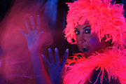 Portrait of a woman wearing a glowing wig with a hand surrounded by a spiritual light.Black light