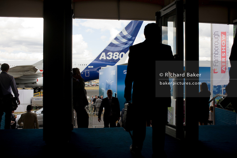 Busy visitors and delegates exit and enter the Farnborough Airshow with the massive Airbus A380 tail in the background.