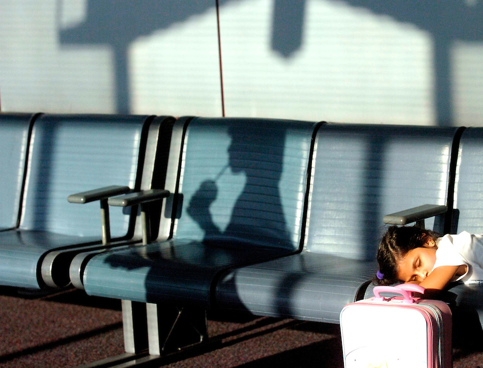 Awaiting a flight at Chicago's Cardinal O'Hare airport, a young girl slumbers as another woman passes by sipping on a straw.