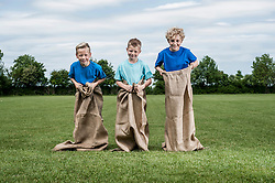 Three young boys preparing for sackrace