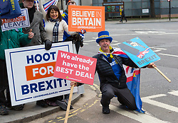 A cheeky Steve Bray, Leader of SODEM (Stand of Defiance European Movement) jumps in front of Leave Means Leave campaigners' banners with his ant-Brexit messages. London, January 14 2019.