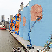 An aerial view as artists Eric Henn, on the front lift, and Dean Davis, at back, work on the Glass City River Wall mural on the ADM grain silos in East Toledo on Thursday, Oct. 14, 2021. THE BLADE/KURT STEISS