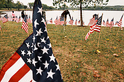 10 SEPTEMBER 2020 - DES MOINES, IOWA: About 25 volunteers braved cold and rainy weather Thursday to line the west end of Gray's Lake in Des Moines with American flags. The display of flags was a part of an annual event called the 9/11 Tribute Trail. About 3,000 flags were set out in memorial of the 3,000 people killed in the 9/11 terrorist attacks.     PHOTO BY JACK KURTZ