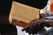 Close up shot of the Imam holding his copy of the Muslim holy book, The Koran, during a class for the children of Kouakourou Village, Mali. Material World Project.