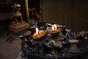Butter lamp burns as offerings at Swayambhunath Temple, Kathmandu, Nepal.