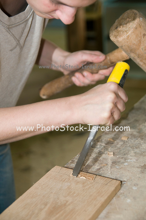 Female carpenter uses a chisel to cutout a dovetail joint