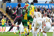 Swansea City goalkeeper Lukas Fabianski (1) punches clear from Norwich's Cameron Jerome (10) and Steven Naismith (7). Barclays Premier league match, Swansea city v Norwich city at the Liberty Stadium in Swansea, South Wales on Saturday 5th March 2016.<br /> pic by  Carl Robertson, Andrew Orchard sports photography.