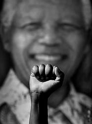 Dec. 12, 2013 - Pretoria, South Africa - A man raises a fist in support of Mandela, in front of a portrait of him. South Africans grieve loss of their leader, Nelson Mandela.<br />