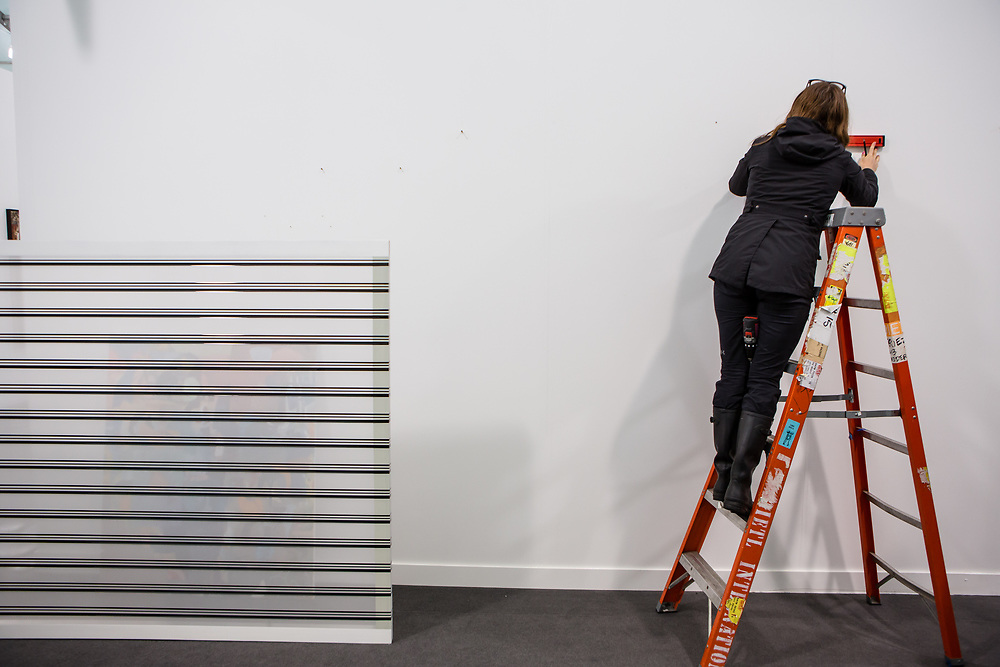 New York, NY - 5 May 2017. The opening day of the Frieze Art Fair, showcasing modern and contemporary art presented by galleries from around the world, on Randall's Island in New York City. A worker prepares to move a painting by Carsten Nicole in the Galerie Eigen + Art after a leak in the roof of the venue threatened the paintings.