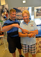 Seaford, New York, U.S. 20th July 2013. Legislator ROSE WALKER, Nassau County LD 17, at right, is holding ZIZOU, a corn snake, and behind her is a display of moon art by Long Island artists, at Science Exploration Moon Day, presented by Long Island Fringe Festival 5, which was hosted by Tackapausha Museum and Preserve.