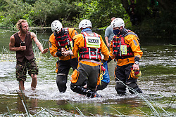 Denham, UK. 24 July, 2020. Police officers from Hampshire Police Marine Support Unit remove a female activist from HS2 Rebellion from the river Colne for arrest after she had tried to hinder the destruction of an ancient alder tree in connection with works for the HS2 high-speed rail link in Denham Country Park. A large policing operation involving the Metropolitan Police, Thames Valley Police, City of London Police and Hampshire Police as well as the National Eviction Team was put in place to enable HS2 to remove the tree.