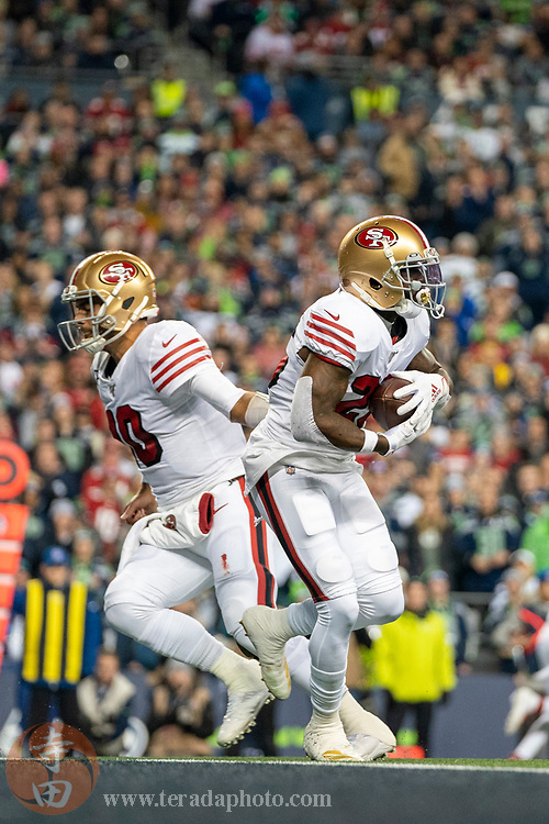 December 29, 2019; Seattle, Washington, USA; San Francisco 49ers quarterback Jimmy Garoppolo (10) hands the football off to running back Tevin Coleman (26) during the first quarter against the Seattle Seahawks at CenturyLink Field.